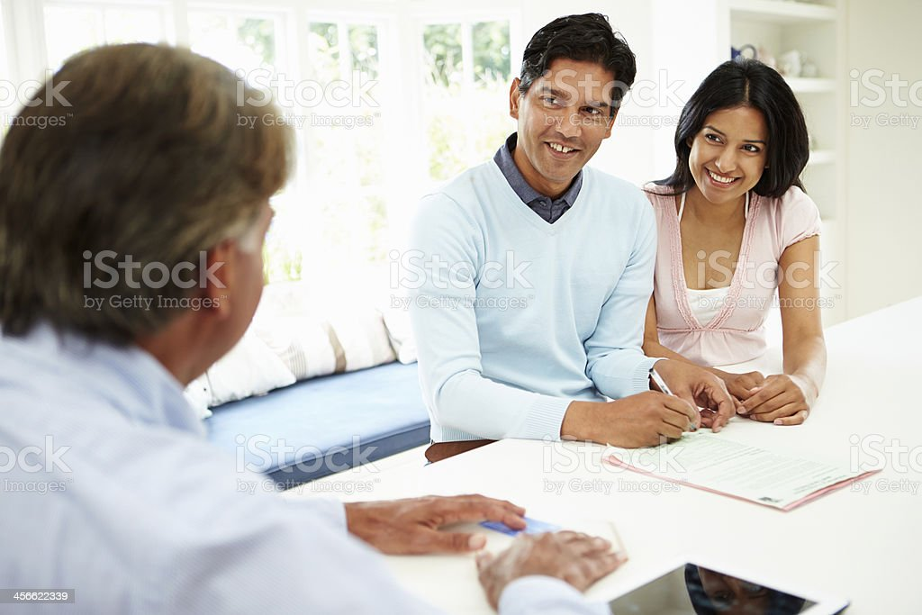 Indian Couple Meeting With Financial Advisor At Home stock photo