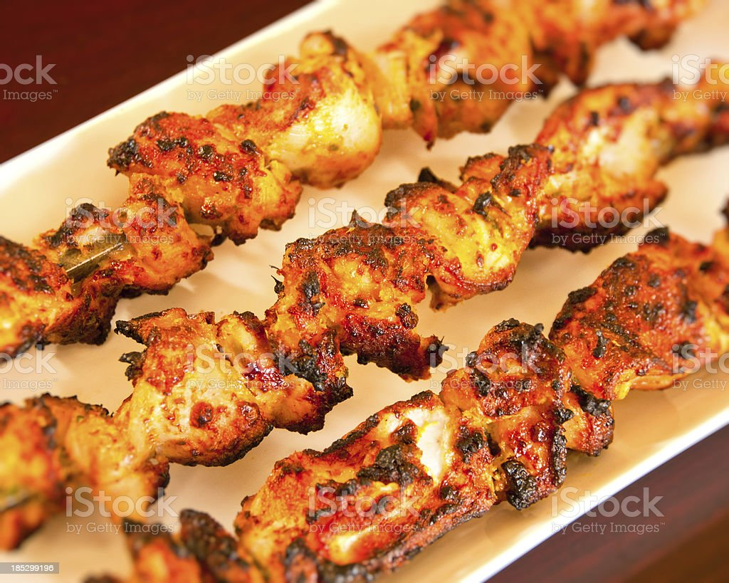 Indian cuisine chicken kebabs on skewers over white platter royalty-free stock photo