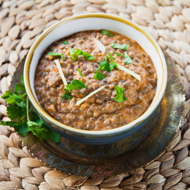 Indian Cuisine Dal Slow cooked creamy Indian curry with Black lentils, sweet spices and Red kidney beans served with coriander cilantro, plant-based cream and ginger. dal makhani stock pictures, royalty-free photos & images