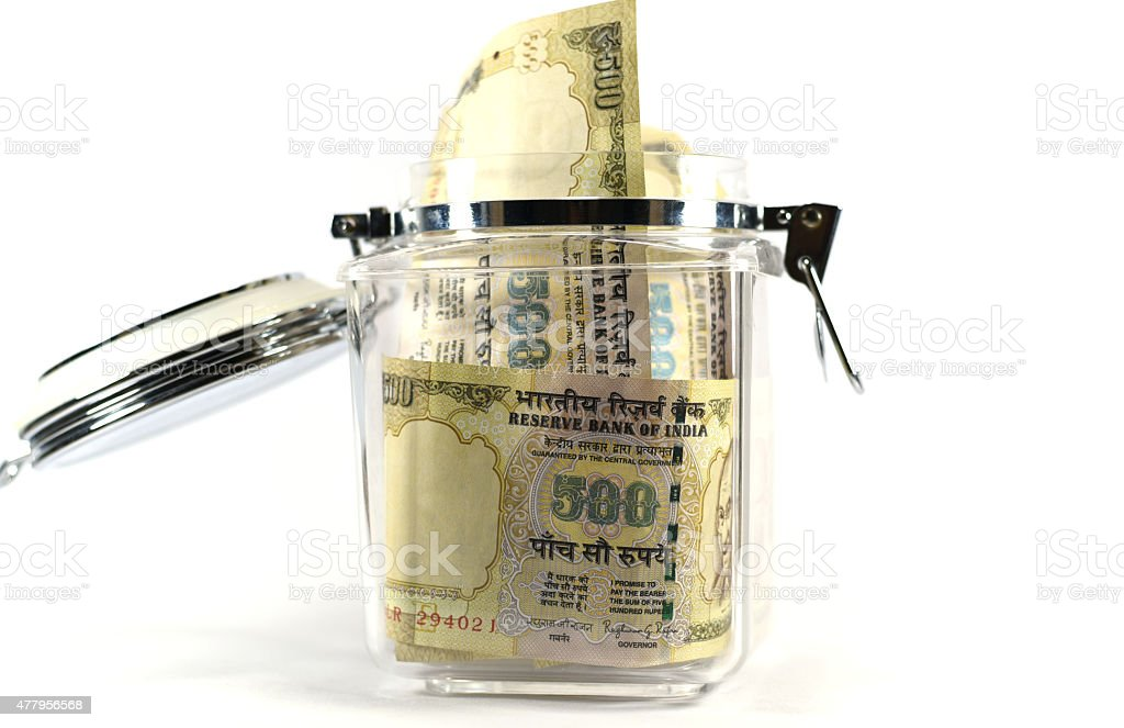 Indian currency notes or 500 Rupee notes in glass jar stock photo
