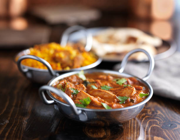 Indian curry - Butter chicken in balti dish indian butter chicken curry in balti dish with naan and biriyanai in background balti dish stock pictures, royalty-free photos & images