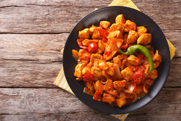 Indian curry Chicken Jalfrezi with spices, tomato sauce and capsicums. horizontal top view stock photo