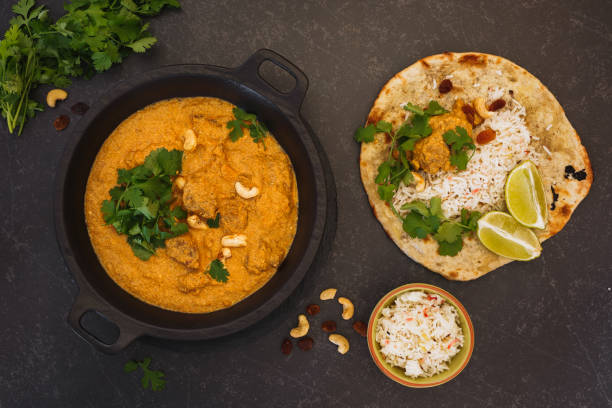Indian curry meal, lamb korma with cashew nuts, rice and peshwari naan Indian curry meal, lamb korma with cashew nuts, rice and peshwari naan, top view, blank space balti dish stock pictures, royalty-free photos & images