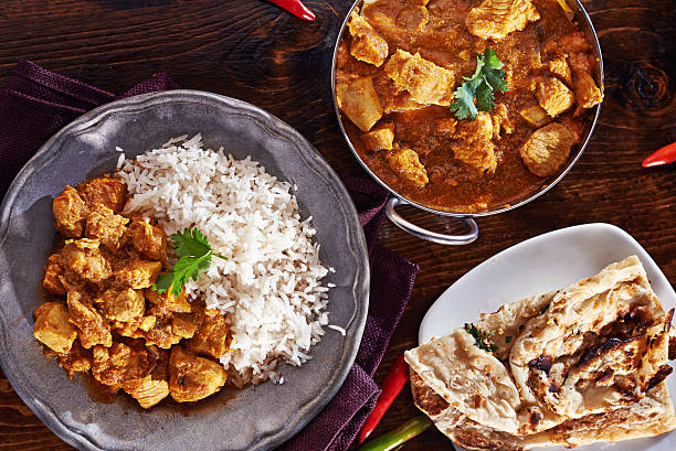 indian curry meal with balti dish, naan, and basmati rice assorted indian curry meal with balti dish, naan, and basmati rice shot from a bird's eye view. balti dish stock pictures, royalty-free photos & images