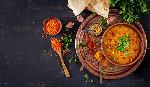Indische dal. Essen. Traditionelle indische Suppe Linsen.  Würzige indische Dhal curry in Schüssel, Gewürze, Kräuter, rustikale schwarzem Holz. Ansicht von oben. Authentische indische Küche. Overhead. Flach zu legen – Foto