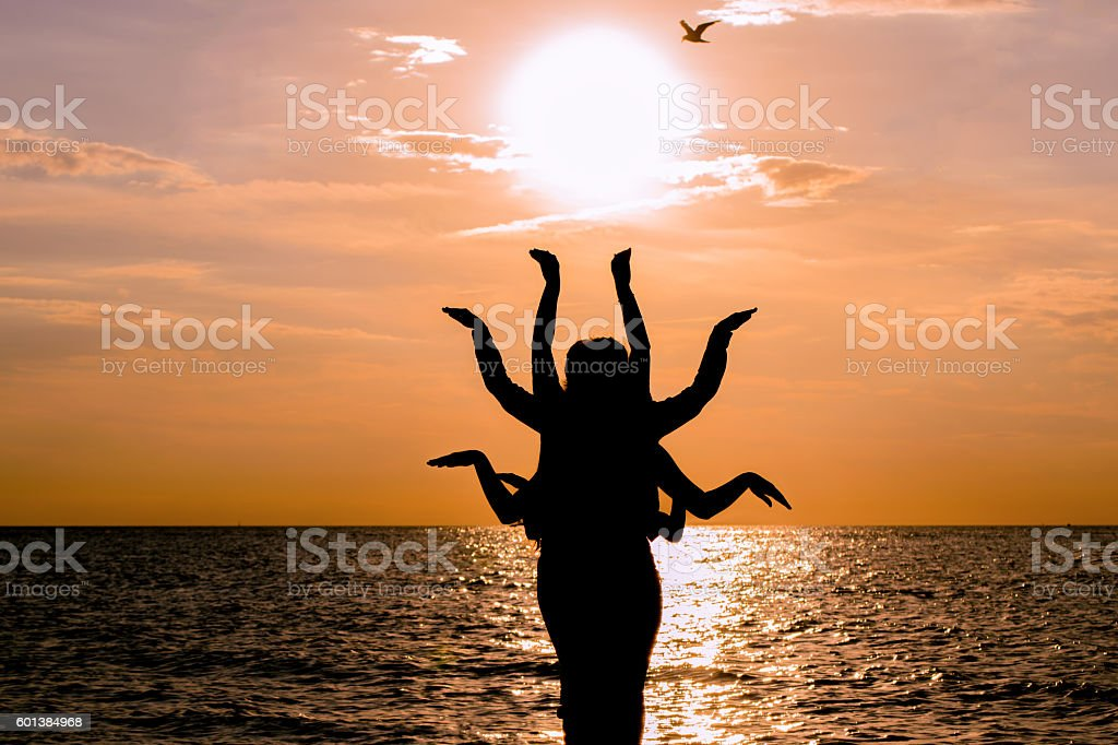 Indian dance silhouette on beautiful beach during sunset. stock photo