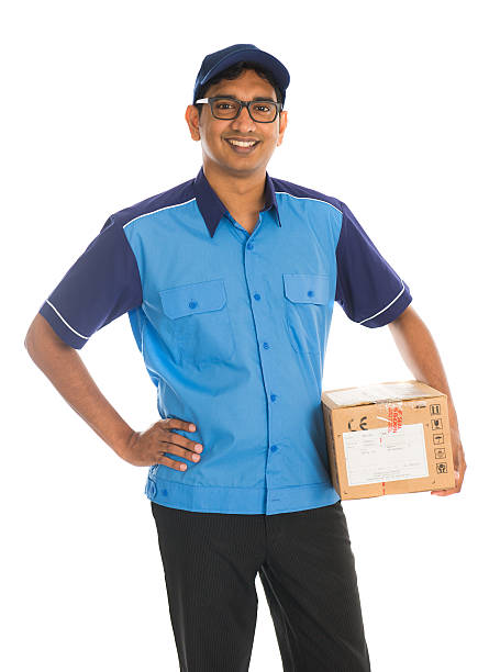 indian delivery man in blue uniform stock photo