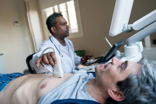 indian doctor doing a heart ultrasound to a middle aged male patient - ultrasound stock photos and pictures