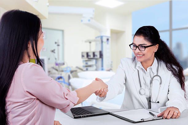 Indian doctor handshake with her patient stock photo