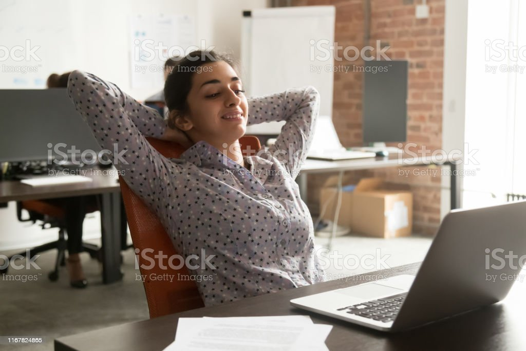 In coworking room worker indian ethnicity girl leaning on office...