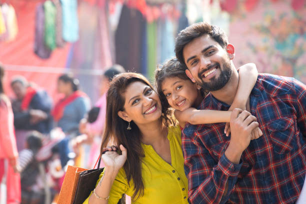 indische familie auf dem straßenmarkt - indische kultur stock-fotos und bilder