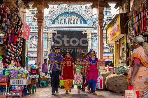 Madurai, Tamil Nadu / India - January 14, 2016: an Indian family walks through an arch occupied by shops, with famous Meenakshi Temple (also known as Meenakshi Amman or Meenakshi-Sundareshwara Temple) in the background. The temple is the main tourist attraction of the city.