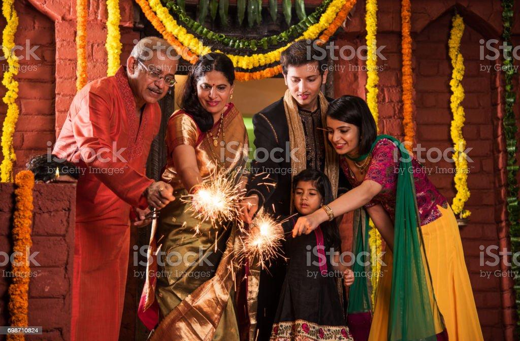 Indian família celebrando festival de Diwali com os biscoitos do fogo - foto de acervo