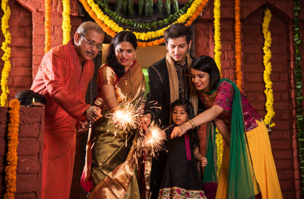 indian family celebrating diwali festival with fire crackers - diwali stock pictures, royalty-free photos & images