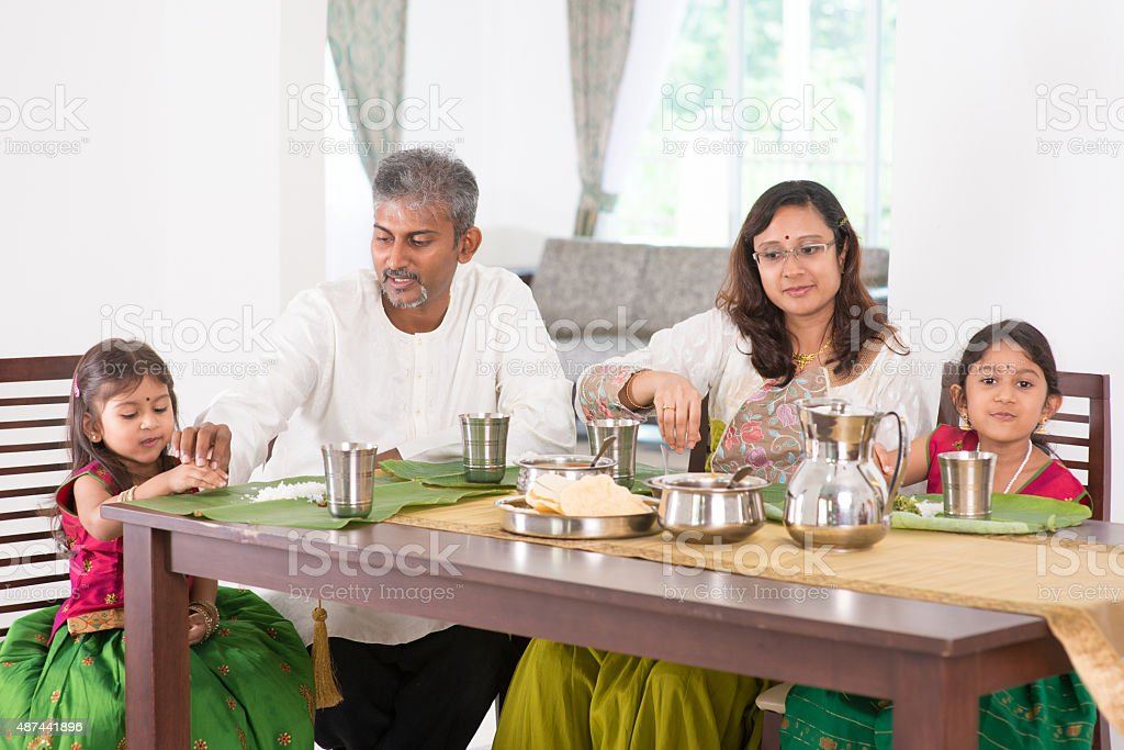 Indian family dining in kitchen stock photo