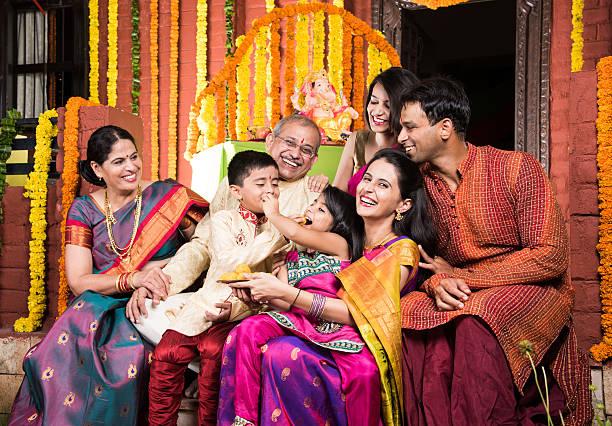 indian family eating sweet laddu on ganesha festival - induismo foto e immagini stock