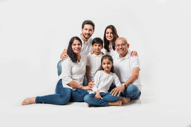 Indian Family isolated over white background indian/asian family sitting over white background. senior and young couple with kids wearing white top and blue jeans. selective focus indian family stock pictures, royalty-free photos & images