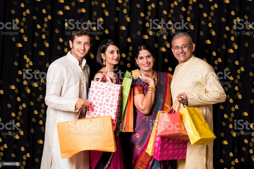 Indian family of 4 with shopping bags standing isolated over black background on diwali with bokeh, senior Indian couple in traditional wear and young kids stock photo