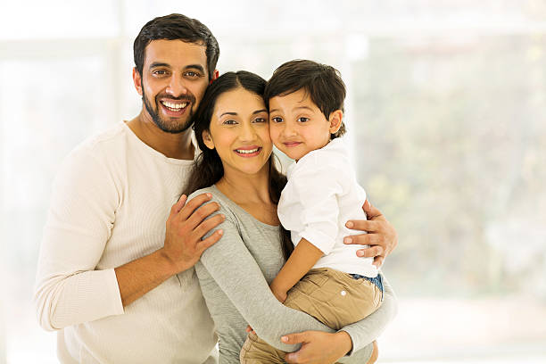 indian family of three portrait of happy indian family of three standing indoors indian family stock pictures, royalty-free photos & images