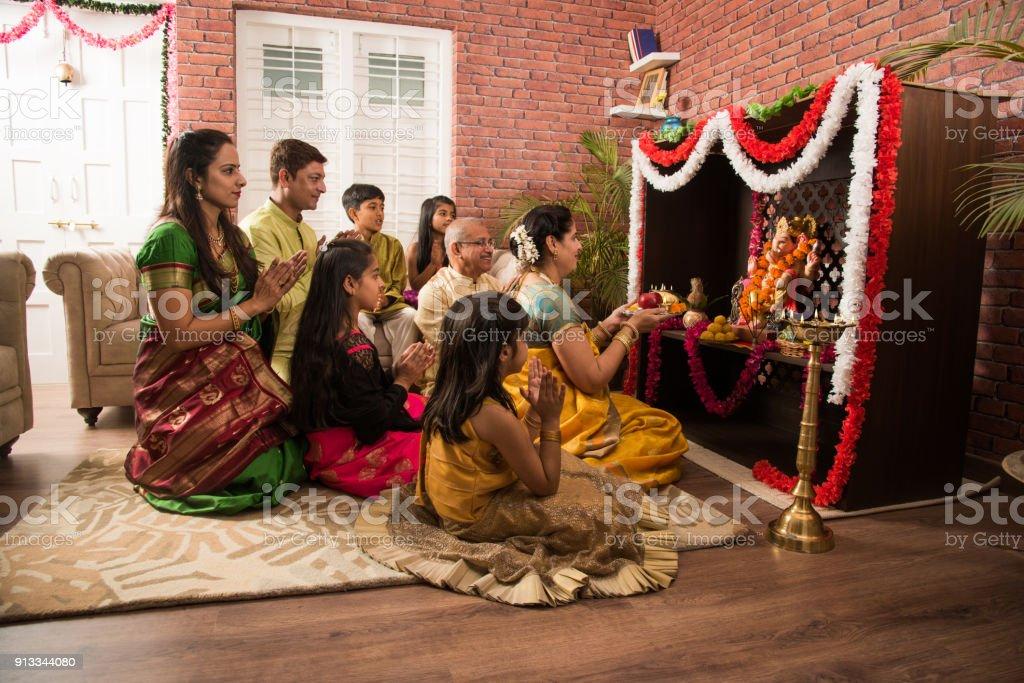 Indian  family performing Ganesh puja or Ganpati Puja in Ganesh Utsav, or holding ganesh idol over white background stock photo