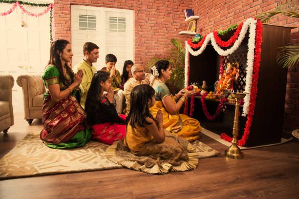 indian  family performing ganesh puja or ganpati puja in ganesh utsav, or holding ganesh idol over white background - induismo foto e immagini stock