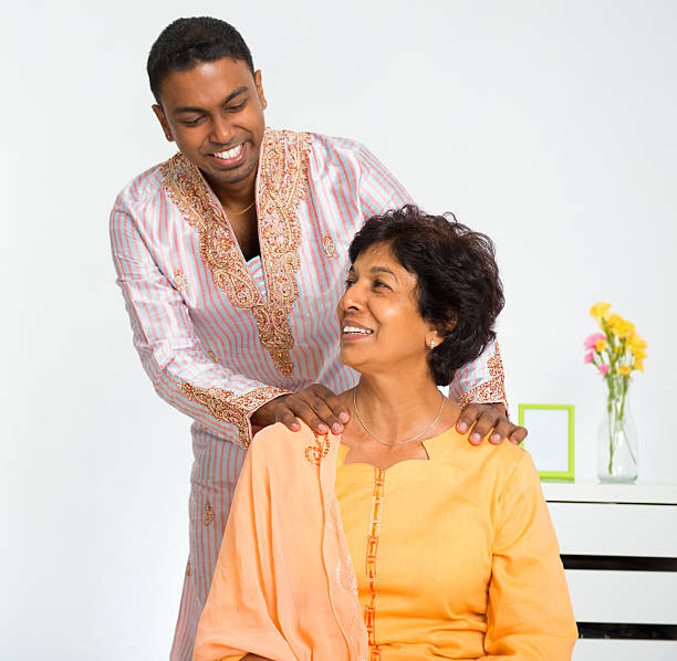 Indian family A lovely mature Indian woman enjoying a shoulder massage from her son at home old mother son asian stock pictures, royalty-free photos & images