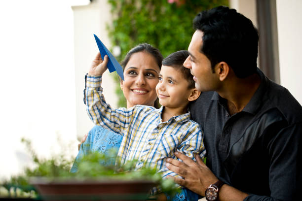 Indian family playing with paper airplane Happy parents with son throwing paper airplane in air indian family stock pictures, royalty-free photos & images