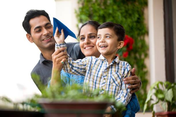 Indische Familie spielt mit Papierflugzeug – Foto