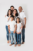 Indian family standing isolated over white background. senior and  young couple with kids wearing white top and blue jeans. selective focus