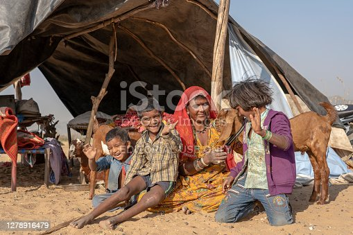 istock Indian family together with a goat outdoors in desert on time Pushkar Camel Mela, Rajasthan, India 1278916479