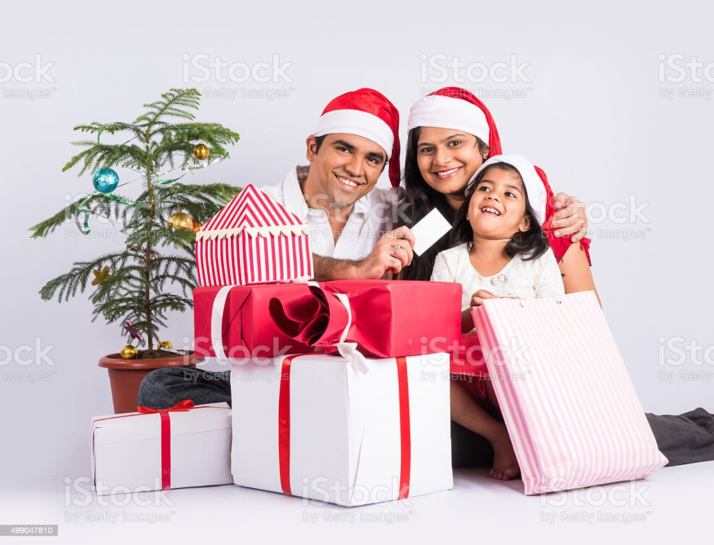 Indian Family With Gifts In Christmas Time Stock Photo & More