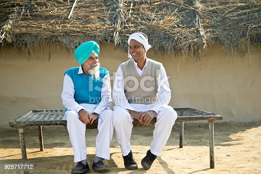 Two Indian farmers discussing on traditional bed outdoors