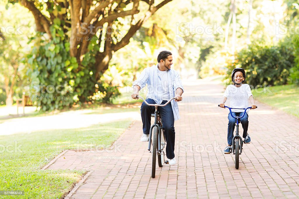 indian father and daughter riding bikes together stock photo