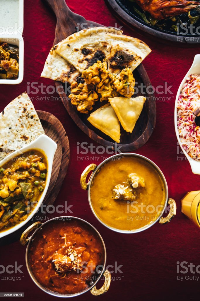 Indian feast with butter chicken, chicken tandoori, lamb curry, vegetable curry, samosas, pakoras, bhajis, naan bread and basmati rice on a table. North Indian food stock photo