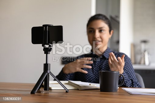 Millennial Indian female vlogger or coach record video live broadcast on smartphone at home. Confident ethnic woman trainer or blogger shoot vlog or course on cell. Online communication concept.