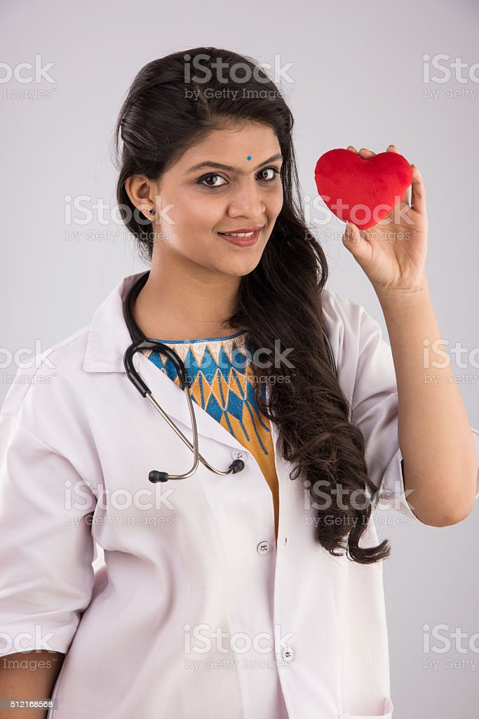 Indian female doctor with red heart toy stock photo