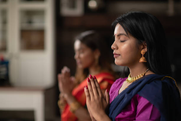 Indian Females Praying One Afternoon in Their Living Room Two (2) Indian sisters are praying in their living room together. They are peaceful as they rest in prayer pose. They are connecting with their god and giving thanks during Diwali. religious celebration stock pictures, royalty-free photos & images