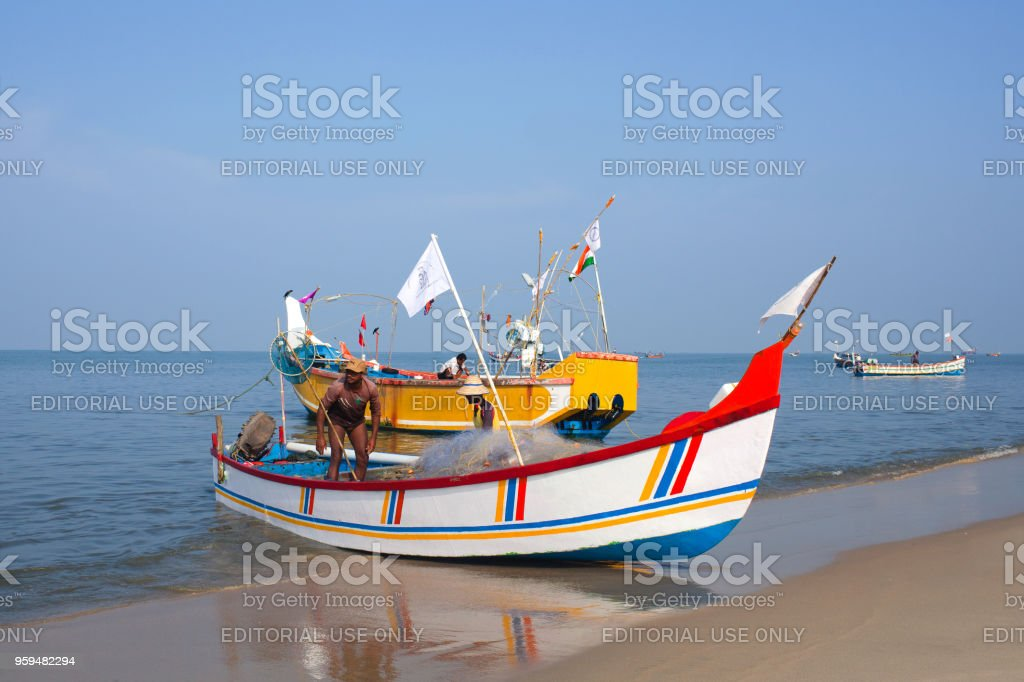 Indian fishermen catching fish for food in wooden boats stock photo