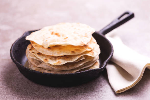 Indian flatbread chapati, green onion. Traditional Kerala Indian cuisine. Homemade flatbread chapati on gray slate background. Copyspace, horizontal view, flatlay. Color surge trend.Traditional Kerala Indian cuisine. Homemade flatbread chapati on gray slate background. naan bread stock pictures, royalty-free photos & images