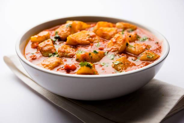 comida indiana - aloo caril masala. batata cozida com especiarias e ervas em um curry de tomate. servido em uma tigela sobre fundo temperamental. foco seletivo - caril - fotografias e filmes do acervo