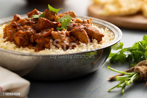 Indian Food - Bowl of chicken vindaloo curry over basmati rice and naan bread.