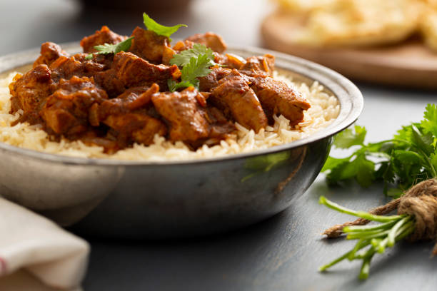 Indian Food Chicken Vindaloo Curry over Basmati Rice Indian Food - Bowl of chicken vindaloo curry over basmati rice and naan bread. curry powder stock pictures, royalty-free photos & images