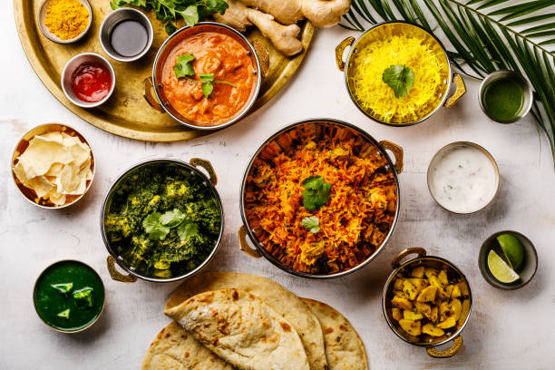 Indian food Curry butter chicken, Palak Paneer, Chiken Tikka, Biryani, Papad, Dal, Rice with Saffron and Naan bread on white background stock photo