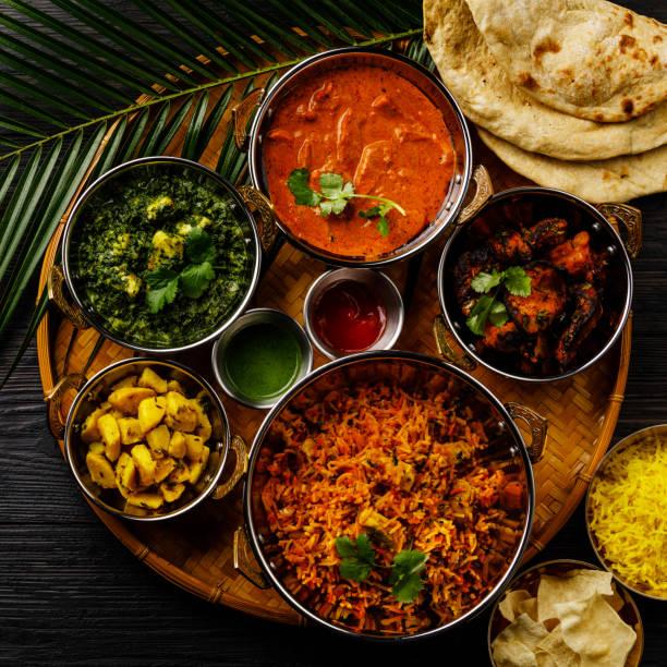 indian food curry butter chicken, palak paneer, chiken tikka, biryani, vegetable curry, papad, dal, palak sabji, jira alu, rice with saffron on dark background - indian food stock pictures, royalty-free photos & images