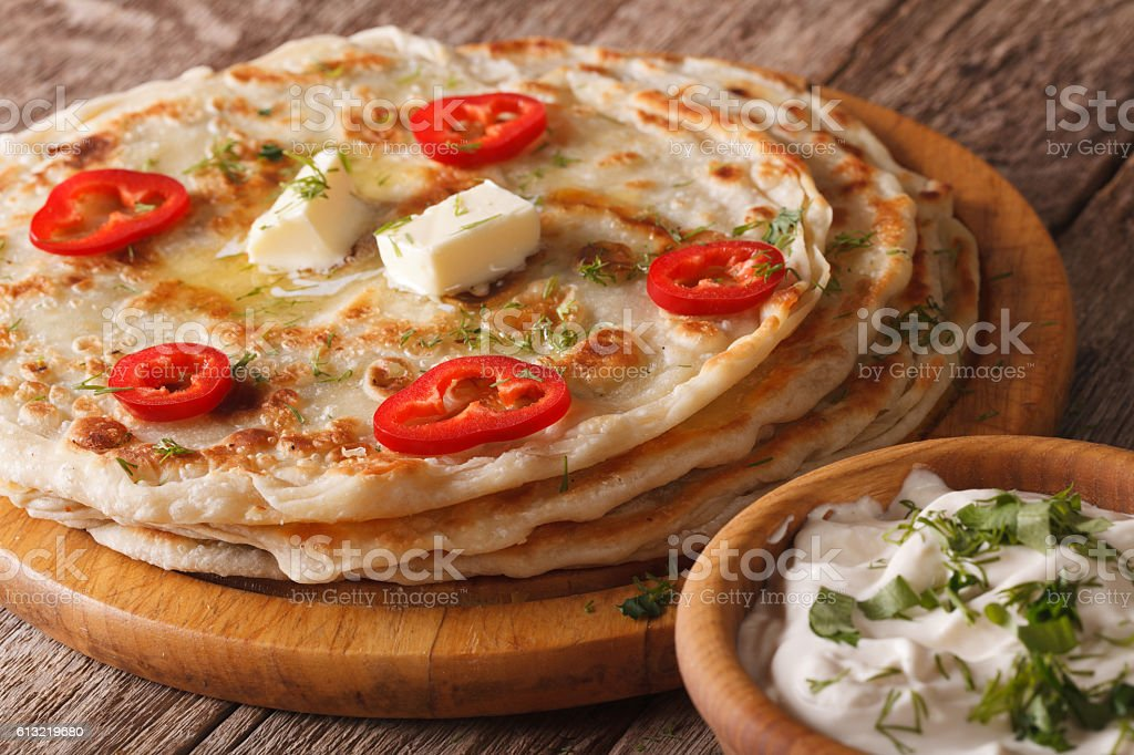 Indian food: hot paratha with butter close-up. Horizontal stock photo