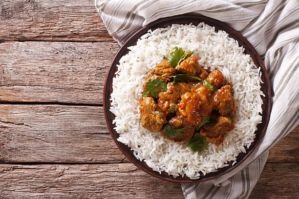 Indian food: Madras beef with basmati rice. Horizontal top view Indian food: Madras beef with basmati rice on the table. horizontal view from above basmati rice stock pictures, royalty-free photos & images