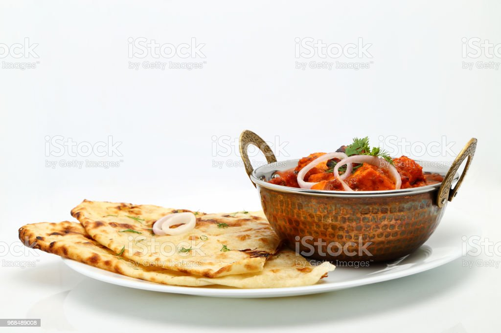 Indian Food or Indian Curry in a copper brass serving bowl with bread or roti. stock photo