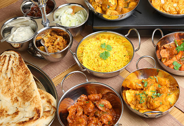 Indian Food Selection Indian chicken, prawn and vegetable curries with naan bread, rice and pickles. balti dish stock pictures, royalty-free photos & images
