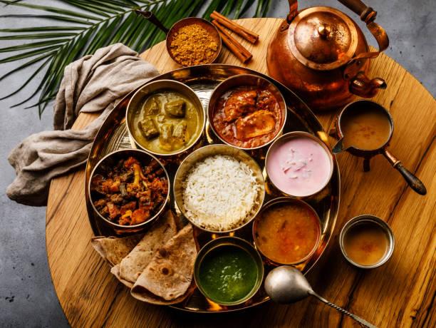 インド料理マサラ紅茶チャイ木製のテーブルや鶏肉とターリー インド スタイルのお食事 - カレー ストックフォトと画像