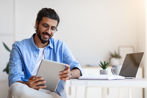 Indian Freelancer Guy Using Digital Tablet At Home, Having Break In Work, Sitting At Desk, Browsing Internet Or Social Media, Checking New App, Smiling Western Man Messaging Or Shopping Online